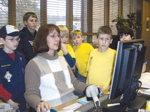 Melissa Soderstrom reviews how tax payments are applied as Jacob Stauffer, Trevor and Jake Carlson, Sean McLellan, Nathan Triesenberg and Mason Parker watch.