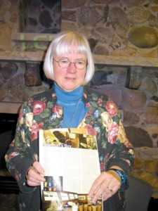 THOUGHTFUL—Sue Osgood shows off a spread her magazine did on Herman's Boy. She explores ways people are finding to enjoy local, hand-produced goods and foods.