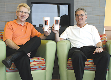 HOT FROM THE COFFEE POT—Bob Sorum and Rich Barnes, toasting their new store with a cup of Biggby's brew, look forward to getting to know their new customers at Biggby Coffee on Ten Mile Road.