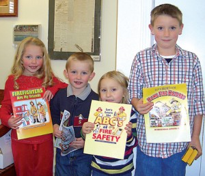 Excited to get started on their activity books provided by the Rockford Fire Department are photo at left (l–r) Brooklyn Vincent, 5, Kenneth Vincent, 3, Alexys Phillips, 4, and Derek Phillips, 8. The activity books are made possible by a fire prevention grant recently awarded