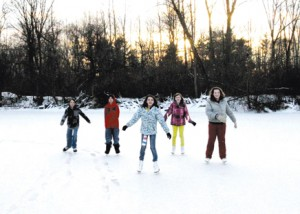 As the sun sets in the west, (pictured l–r) twin brothers Ben and Alex Norkey, 12, Bridgette Davis, 12, Grace Garner, 12, and Lexi Loop 12, all North Rockford Middle School students, are having a blast. They have been skating on the pond regularly since its early freeze-up and especially appreciate the smooth Zamboni-like surface.